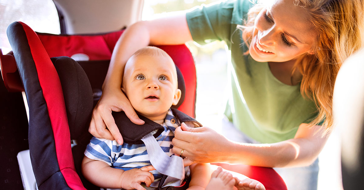 mom strapping baby in car seat