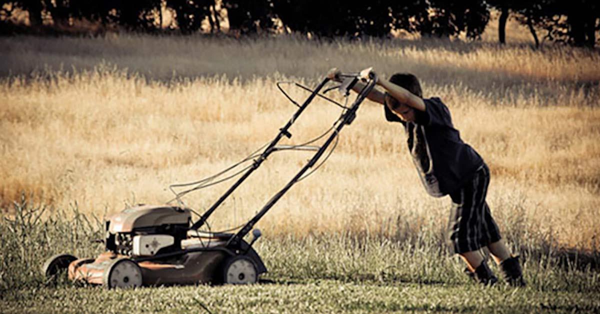 boy mowing a lawn