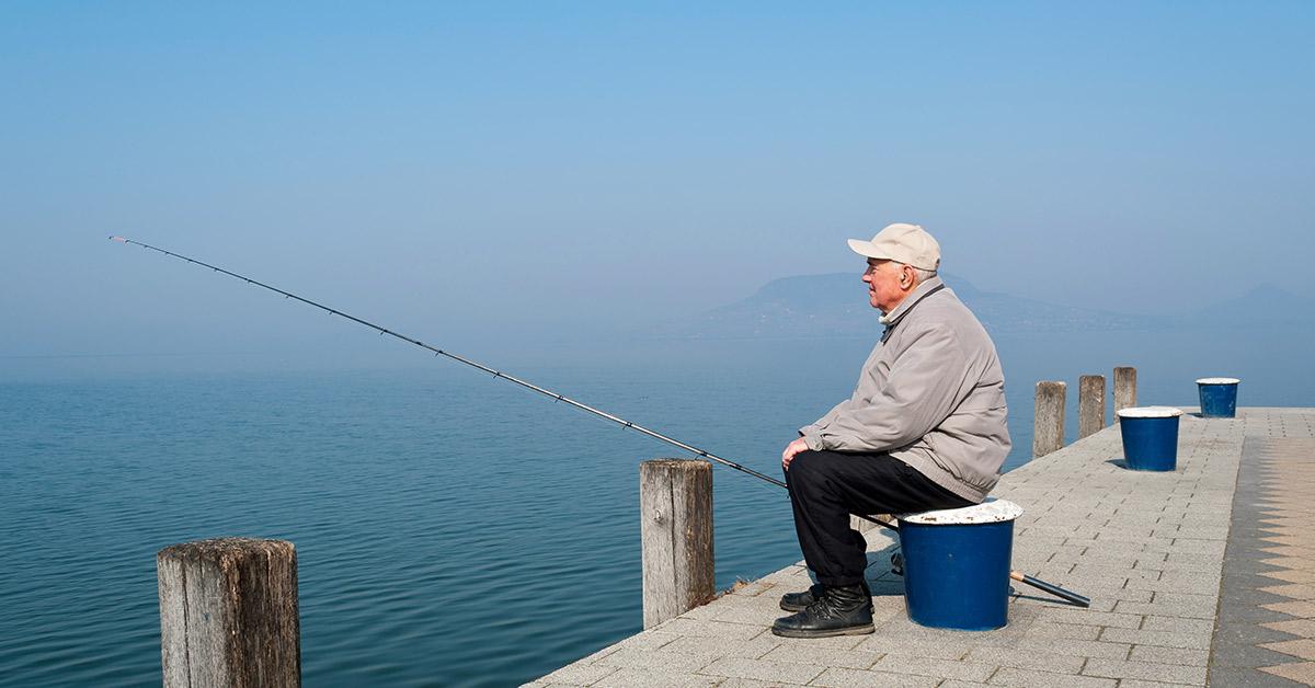 elderly man fishing on doc