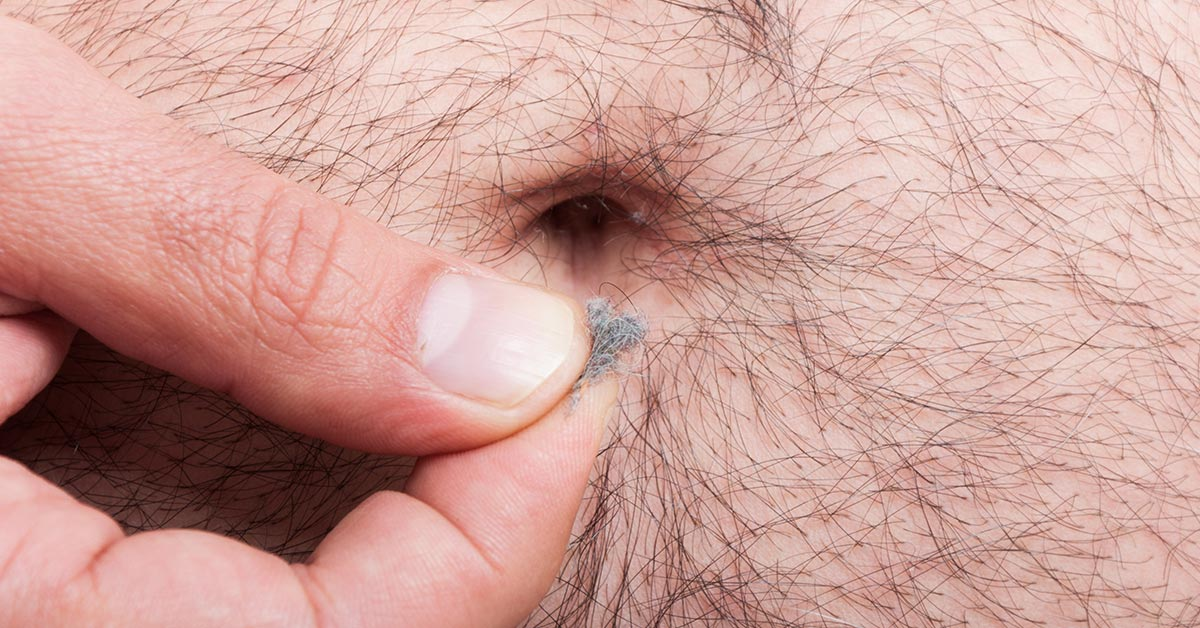 close of of belly button with lint being held between someones thumb and index finger