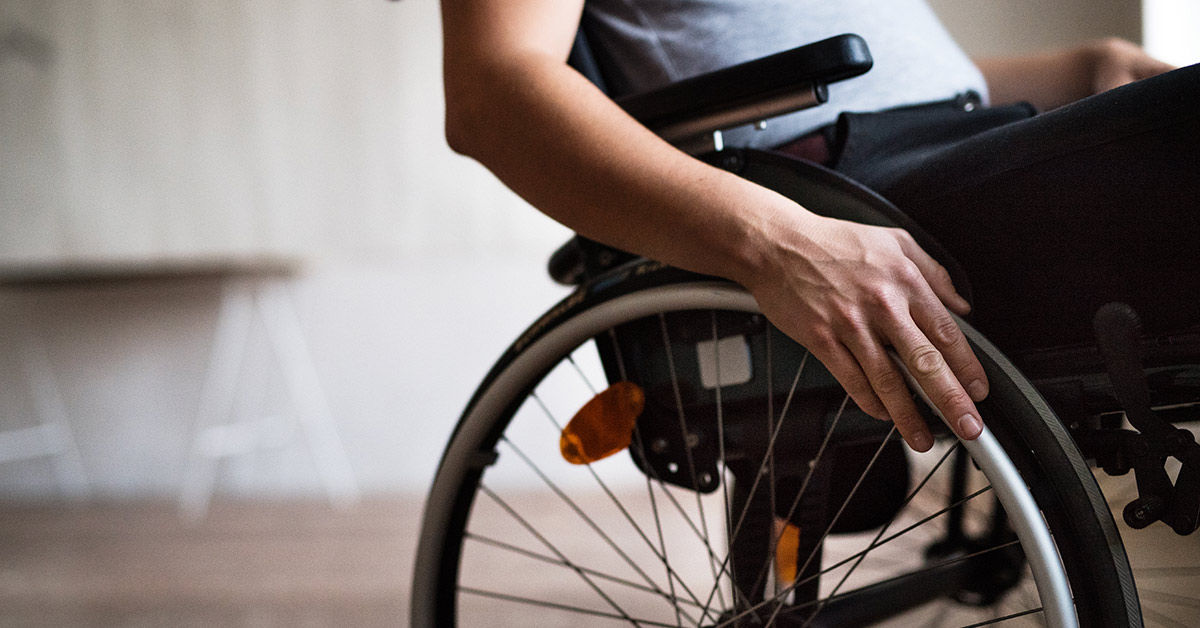 person in a wheelchair with hand placed on wheel