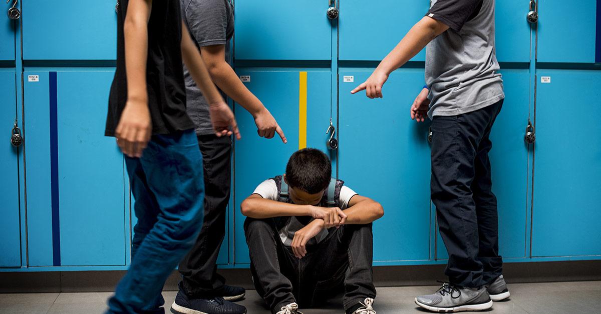tween boy being bullied in school hallway