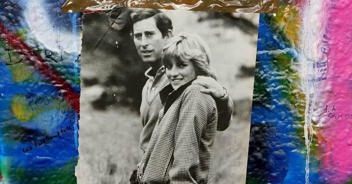 Photo of Princess Diana and Prince Charles taped to a graffiti covered wall